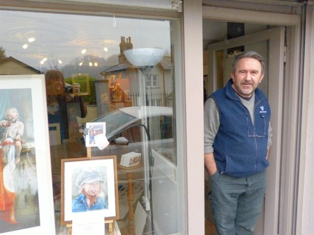 Neil outside his studio in Enniskerry, with a print of 'Upon Small Shoulders' in the window, beside a portrait of the tiny model's beautiful red-headed sister