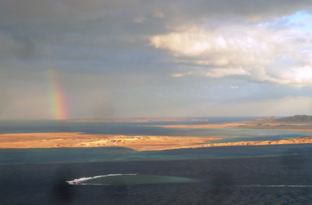 Rainbow with a circular coral reef visible in the foreground