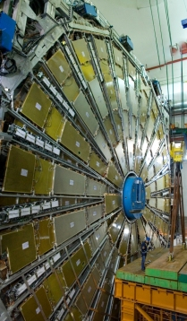 A man beside the detector standing on the huge yellow lift helps gauge the size